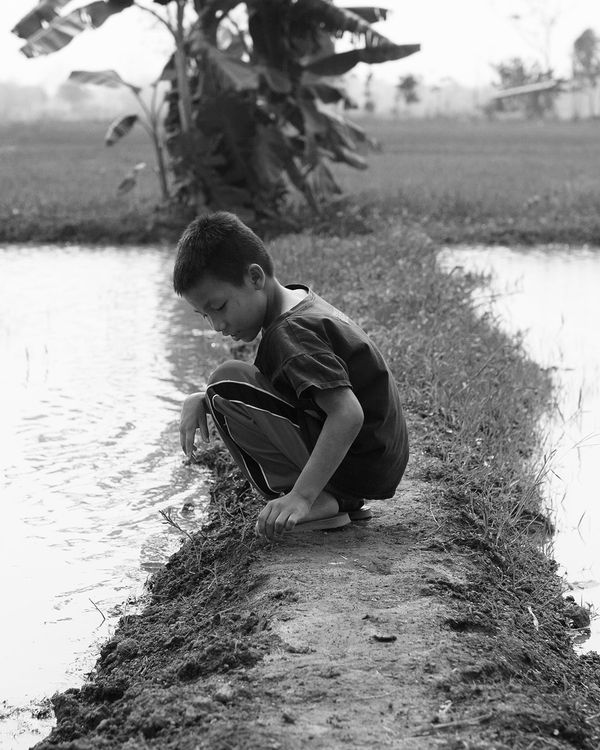 Black and white photo of a street kid playing next to water.