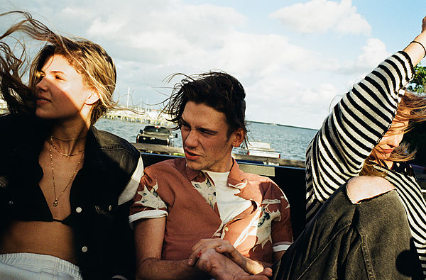 The Road Trip Part 2 - mage in colours of a young guy wearing a Hawaiian style shirt, sitting at the back of a convertible car in between two girls. The left girl wearing a black denim trucker jacket over a black bikini top. The girl on the right hand-side wearing an oversized stripey navy and white jumper.