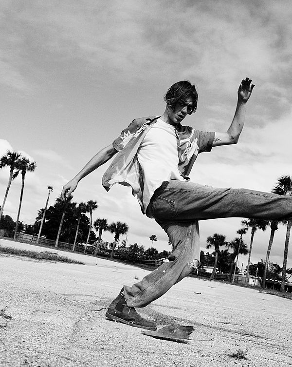 The Road Trip Part 2 - Black and White image of a guy kicking something off the floor and wearing a short sleeve Hawaiian shirt, open over a white t-shirt and denim jeans.