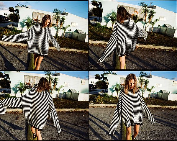 The Road Trip Part 2 - Four different shots of the same girl walking playfully along a line and wearing an oversize striped navy and white jumper over a black long shirt with white polka dots.