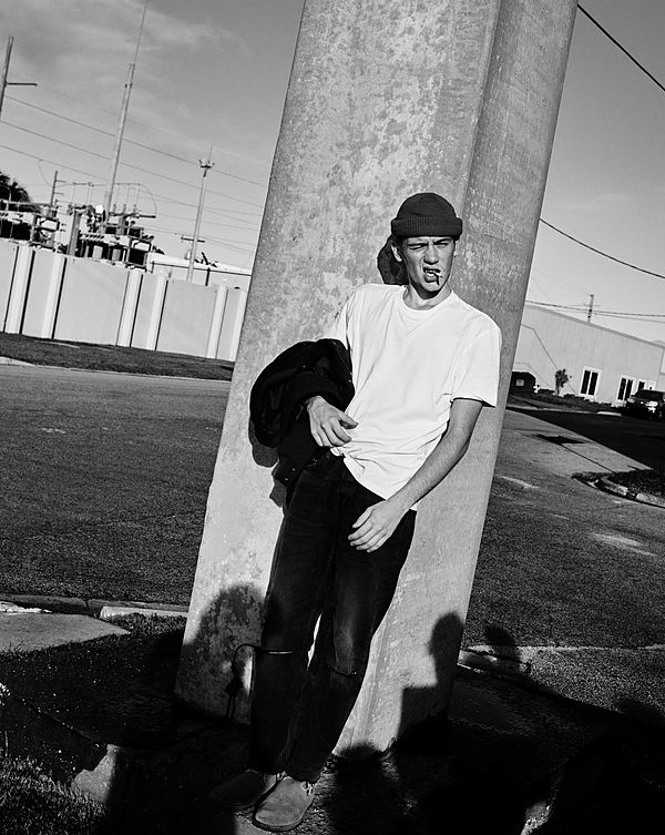 The Road Trip Part 2 - Black & White image of a guy smoking a cigarette while leaning against a pillar in the sun wearing a white T-Shirt and black jeans with splits on the knees, and holding his Bomber jacket.