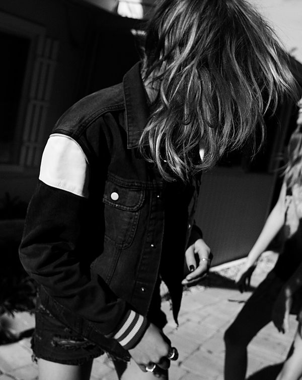 The Road Trip Part 2 - Black & white picture of a girl in the street looking away from the camera and wearing a black denim trucker style jacket with white leather patches on the shoulders with black denim shorts.