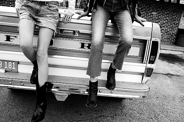 The Road Trip Part 2 - Cropped black & White image of 2 girls sitting at the back of a truck wearing black boots with a denim skirt and a jeans.