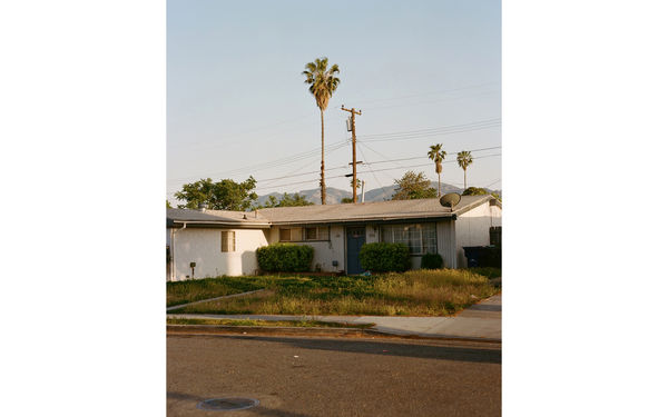 Photo of a house from the street with palm trees in the background