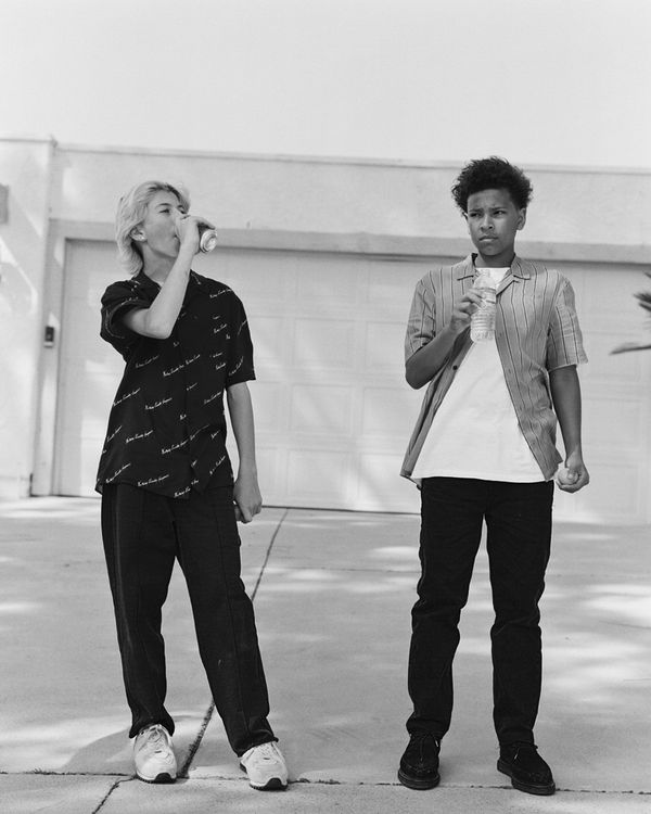 Black and white image of two young men standing in the street and wearing pieces from the latest capsule collection