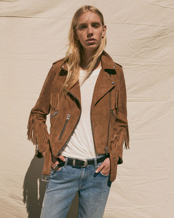 Campaign image of a woman wearing a tan fringed suede jacket from our latest collection, over a white T-Shirt.