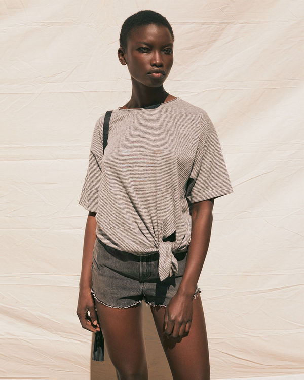 Portrait image of a woman wearing a t-shirt with a knot detail at the front from our latest collection with a pair of dark jean shorts.