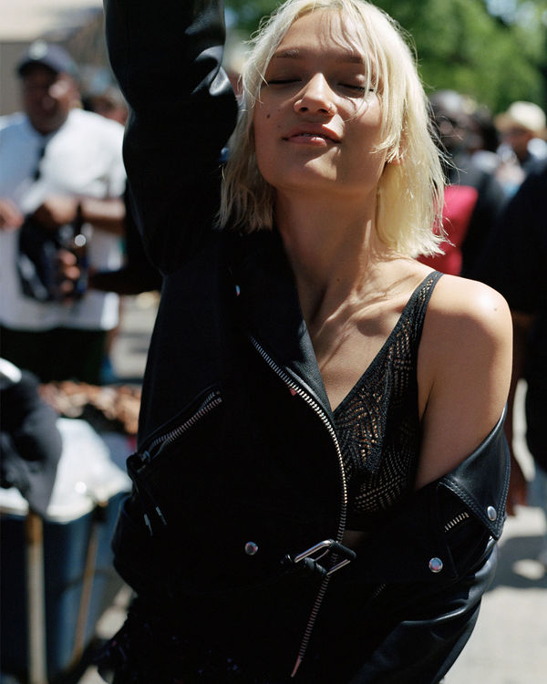 Image of a young woman partying in the street during the day and wearing a black leather jacket dropping on one shoulder.