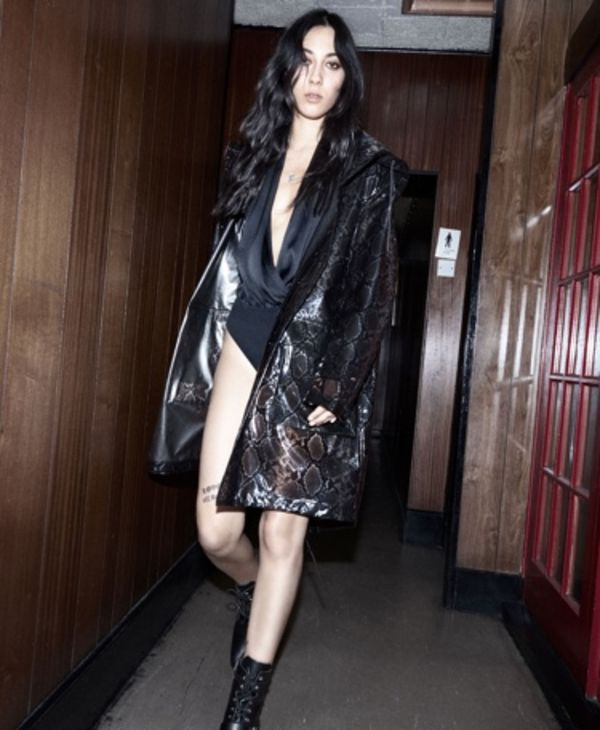Immagine di una donna che cammina lungo un corridoio. Indossa un body nero con un cappotto pitonato e anfibi neri.