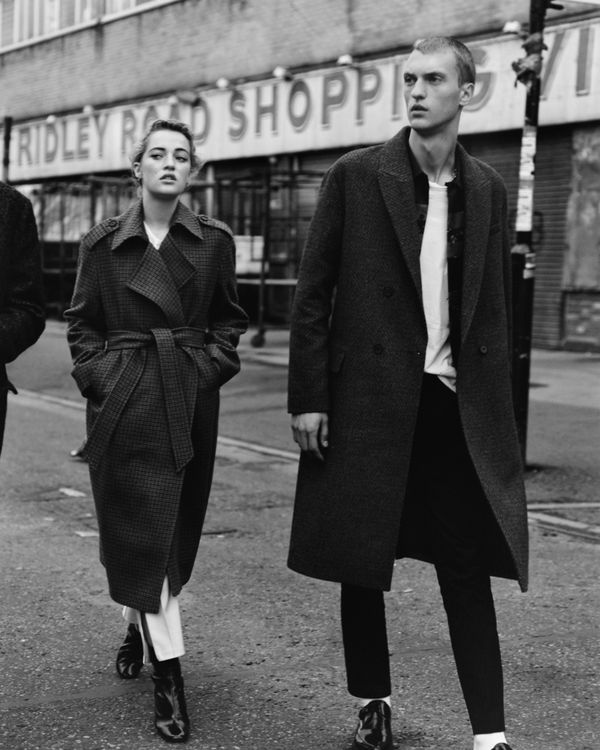 Black and white image of a woman and a man walking in the streets of London and wearing coats from our latest collection.