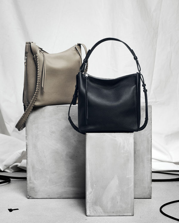 Image of two women's handbags on grey plinths in front of a white background.