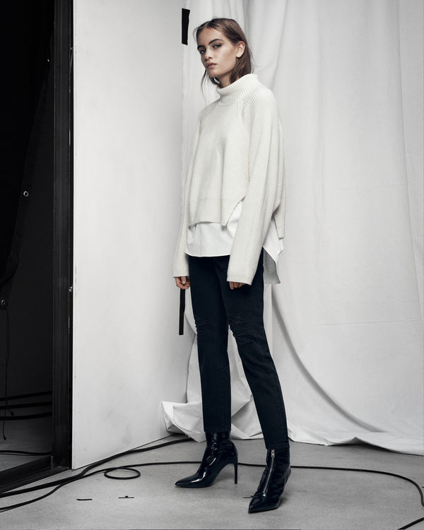 Lookbook image of a woman standing and wearing a white oversized sweater with black tailored pants.