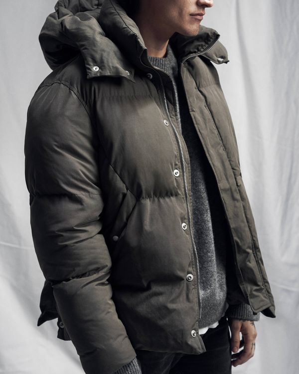Lookbook image of a man wearing khaki puffer jacket opened over a grey jumper.