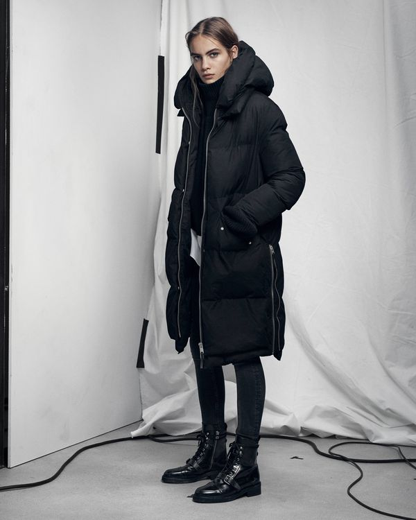 Lookbook image of a woman standing and wearing long black puffer jacket.