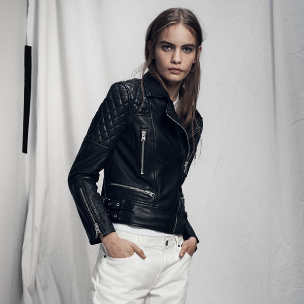 Lookbook image of a woman standing and wearing a black leather jacket and white jeans.
