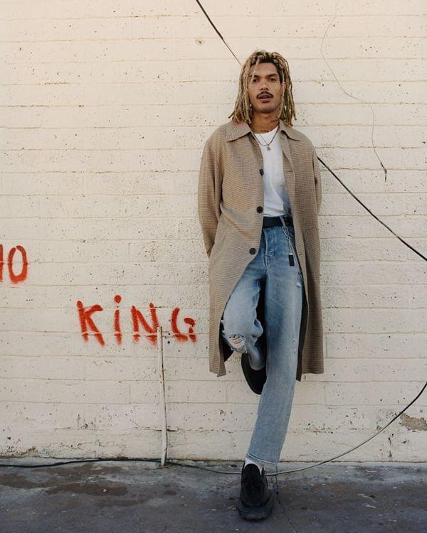 Mann, der gegen eine Wand lehnt und eine Jeans in heller Waschung mit einem weißen T-Shirt und beigem Regenmantel trägt.