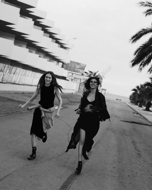 Campaign image of two women running in the street wearing dresses from our latest collection.