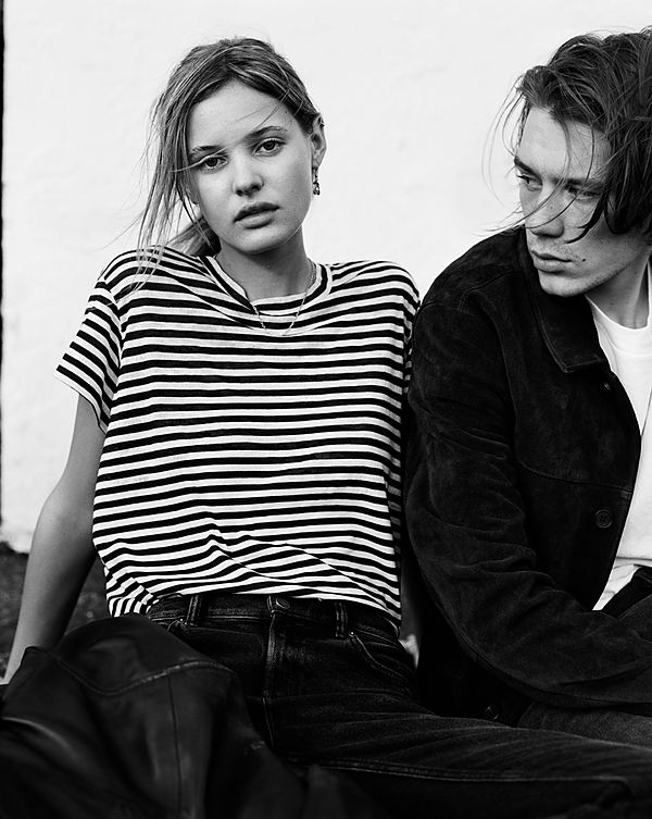 The Road Trip - Black & White image of a girl wearing a striped t-shirt and black jeans and sitting next to a guy wearing a black denim jacket over a white t-shirts and black jeans.