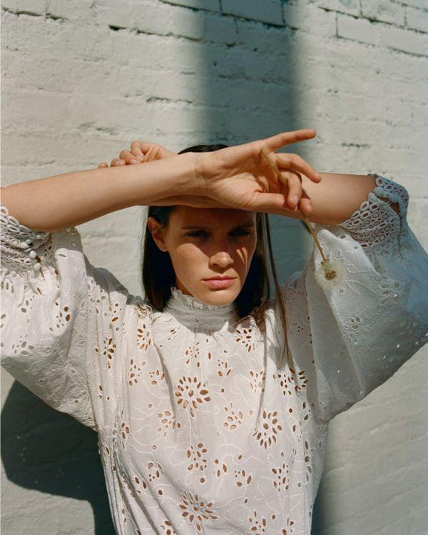 Femme debout devant un mur portant une robe blanche et croisant les bras sur son front tout en tenant une fleur.