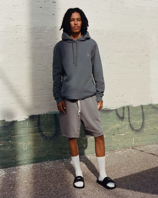 Homme debout portant un sweat à capuche gris avec un sweat-shirt gris et des chaussettes aux genoux blanches.