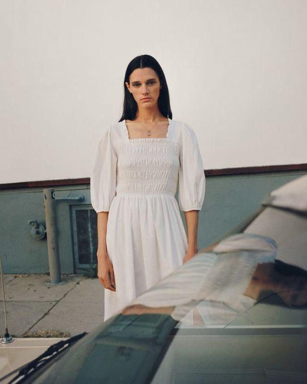 Femme vêtue d'une robe romantique blanche à col carré.
