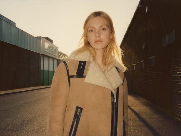 무스탕을 착용한 길거리에 서있는 여성 모델 이미지