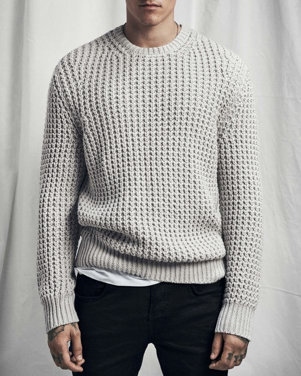 Lookbook image of a man wearing a chunky grey jumper and black jeans.