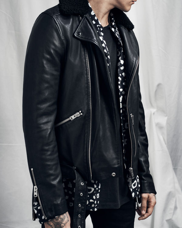 Lookbook image of a man wearing a black leather jacket with a shearling collar, undone over a printed shirt.