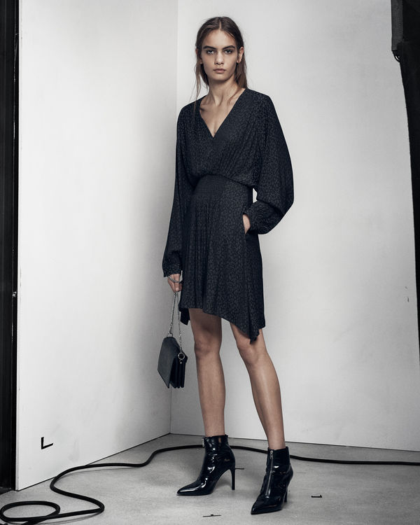 Lookbook image of a woman standing and wearing a black dress from our latest collection, worn with black boots.