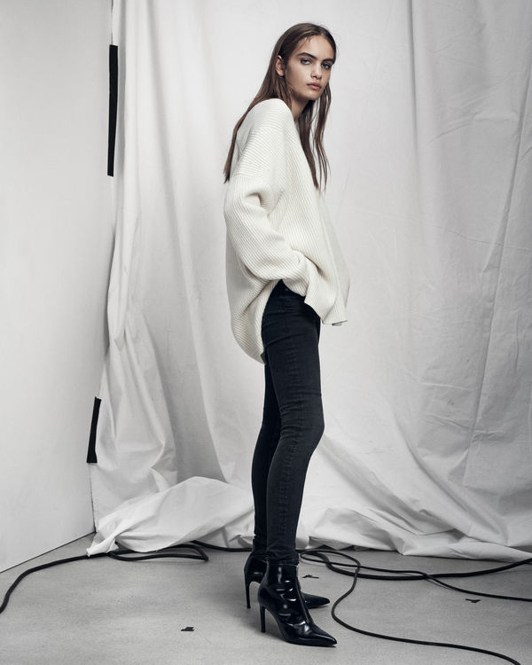 Lookbook image of a woman standing and wearing an oversized white jumper and black jeans.