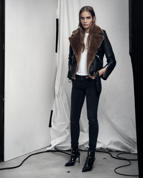 Lookbook image of a woman standing and wearing a black leather jacket with shearling details, with black jeans.