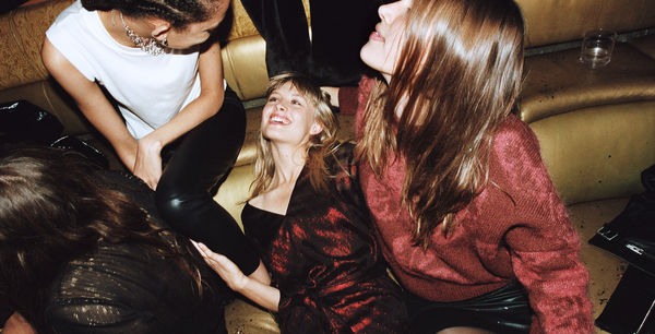 Campaign image of three women sitting on a couch at a party and showcasing our latest collection.
