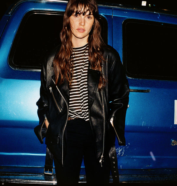 Picture of a woman standing in front of the back of a metalic blue van and wearing a dark leather jacket over a black and white striped t-shirt.