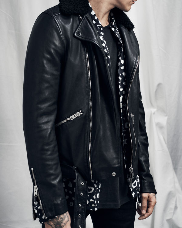 Man wearing a black leather jacket with shearling collar from our latest collection, opened over a printed shirt.