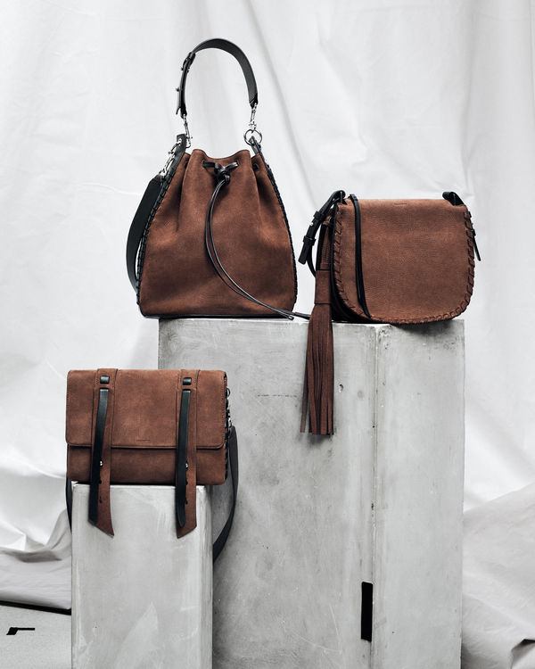 Three suede brown bags from our latest collection on a grey plyth in front of a white background.