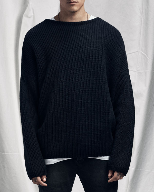 Lookbook image of a man wearing a navy blue jumper from our latest collection.