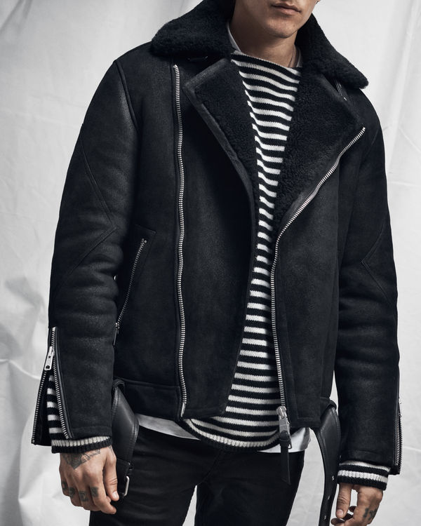 Lookbook image of a man wearing a black shearling jacket from our latest collection over a striped jumper.