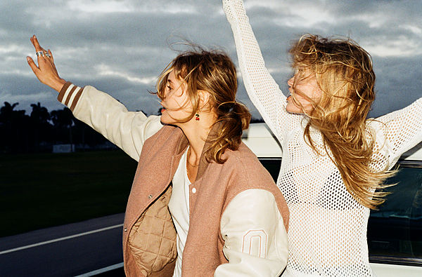 The Road Trip Part 4 - Picture of two blonde girls at the back of a truck in motion. The one on the left wear a white vest under a salmon coloured oversized bomber jacket with white leather sleeves. The girl on the right wears a white mesh long sleeve top over a black triangle bikini top.