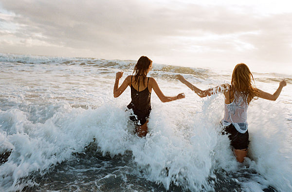 Image of two young women, through ocean waves on the beach.