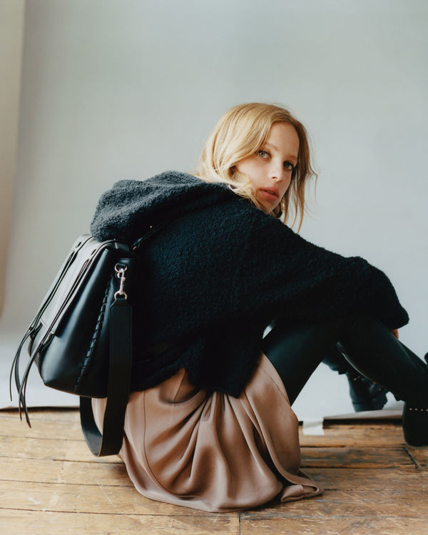 Portrait of a woman sitting on the floor showcasing a black backpack worn over a chunky knitted hoody with a silky dress underneath.