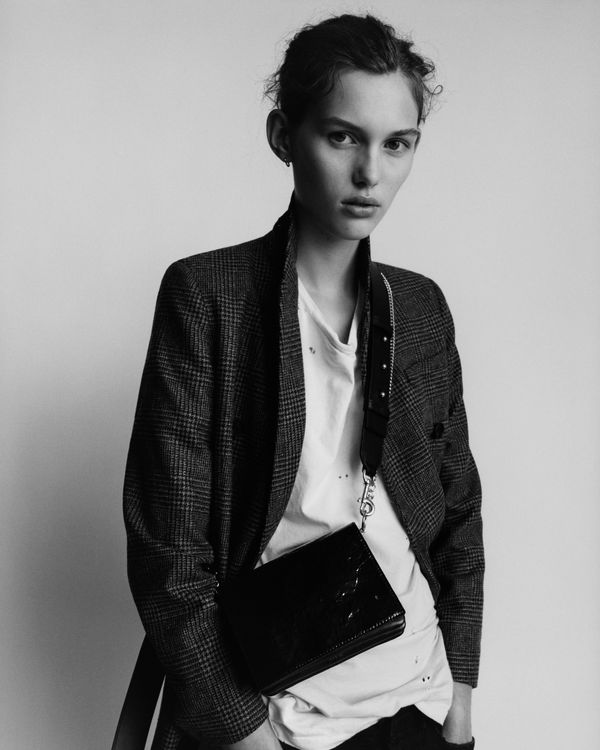 Portrait in black and white of a woman wearing a white t-shirt under a checked blazer and showcasing a small crossbody bag.
