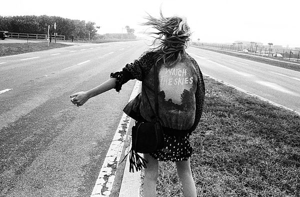 The Road Trip - Black & White image of a girl hitchhiking, seen from the back, wearing a dotted dress, handbag and a bomber jacket with a 'Watch the skies' print