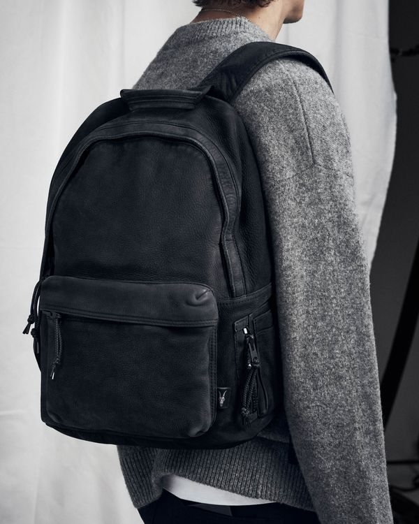 Back shot of a man wearing a grey jumper and showcasing a black backpack from our latest collection.