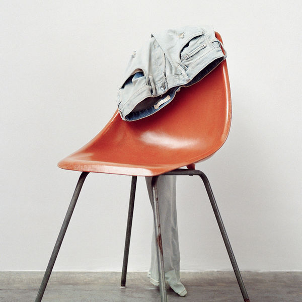 Pair of light grey jeans hanging at the back of an orange chair.