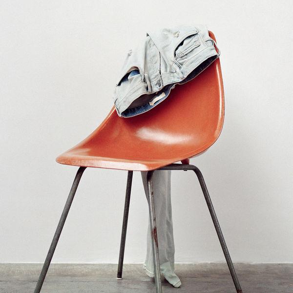 Hell graue Jeans die auf dem Rücken eines orangenen Stuhls hängen.