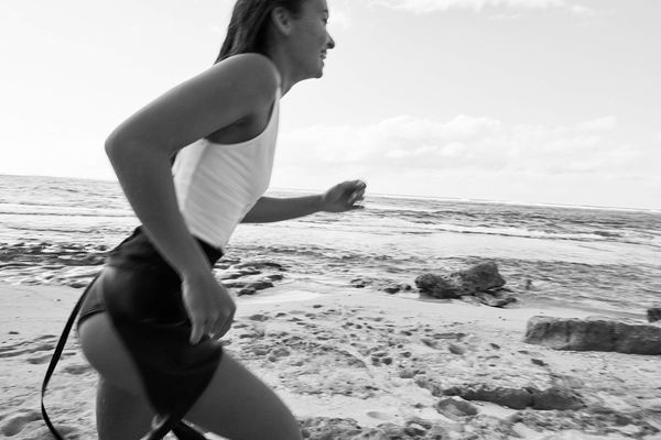 Black and white image of a woman running on the beach wearing a white swimsuit and a wetsuit.