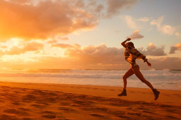 Landscape picture of a woman runinng on the beach with a sunset in the background.