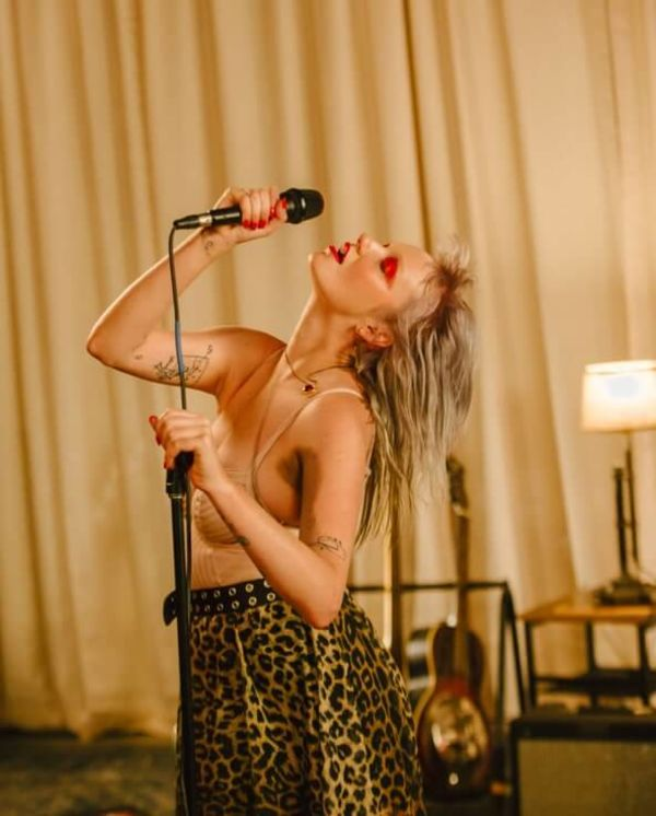 Portrait of Ariel Beesley singing and wearing a leopard print skirt with a pale pink bodysuit.