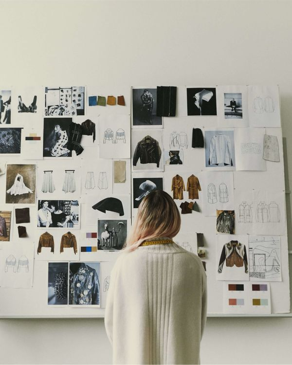 A woman is standing in front of a moodboard wall showing sketch, pictures, and inspiration drawings of leather jackets.