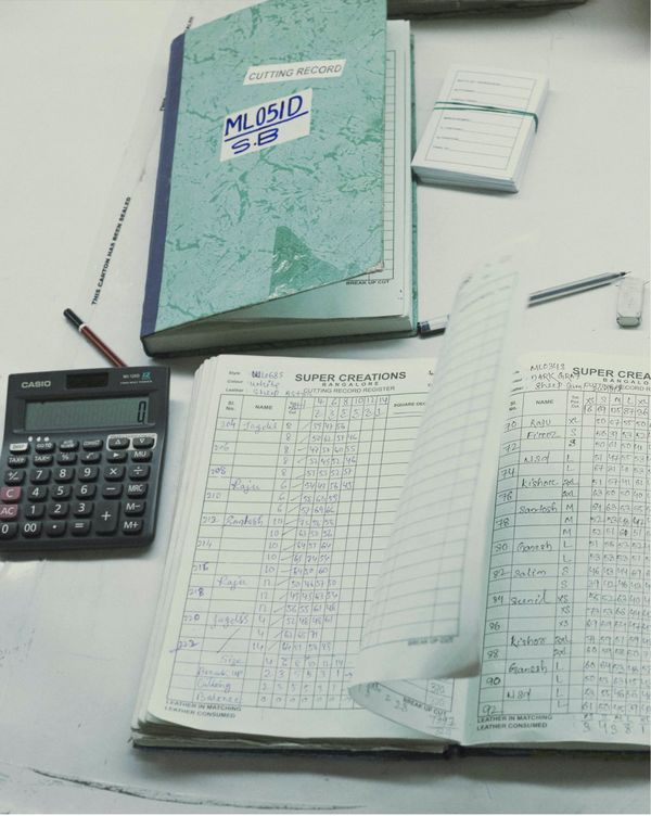 Close up on a quality check form with a notepad and a calculator.